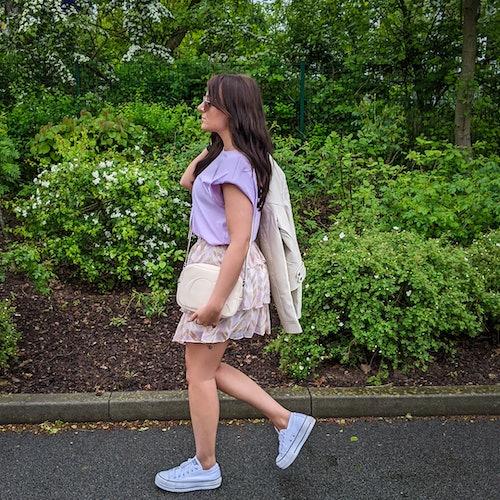 junge Frau in sommerlichem Outfit geht einen Weg entlang