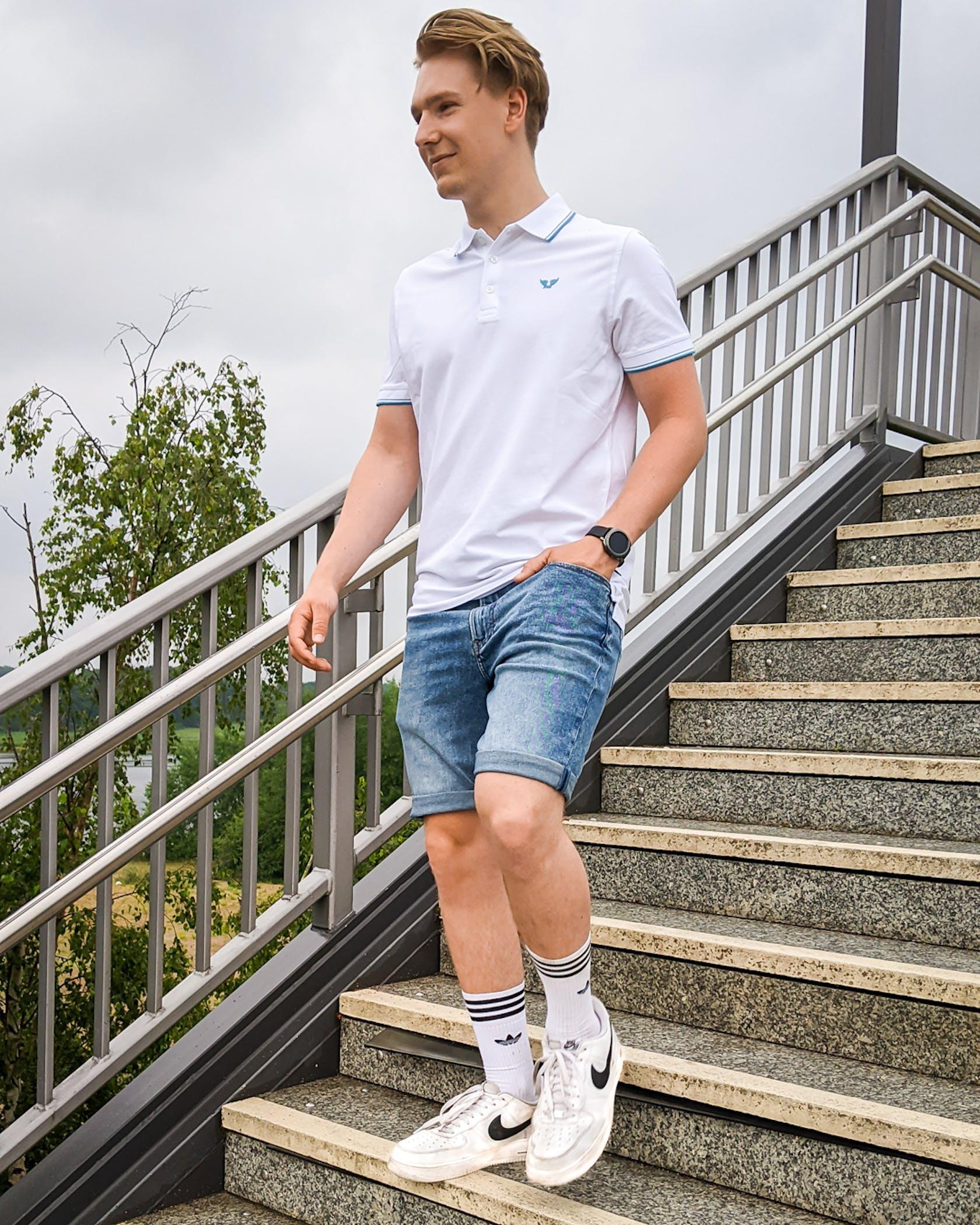 junger Mann trägt ein poloshirt und Jeansshorts und läuft eine Treppe herunter
