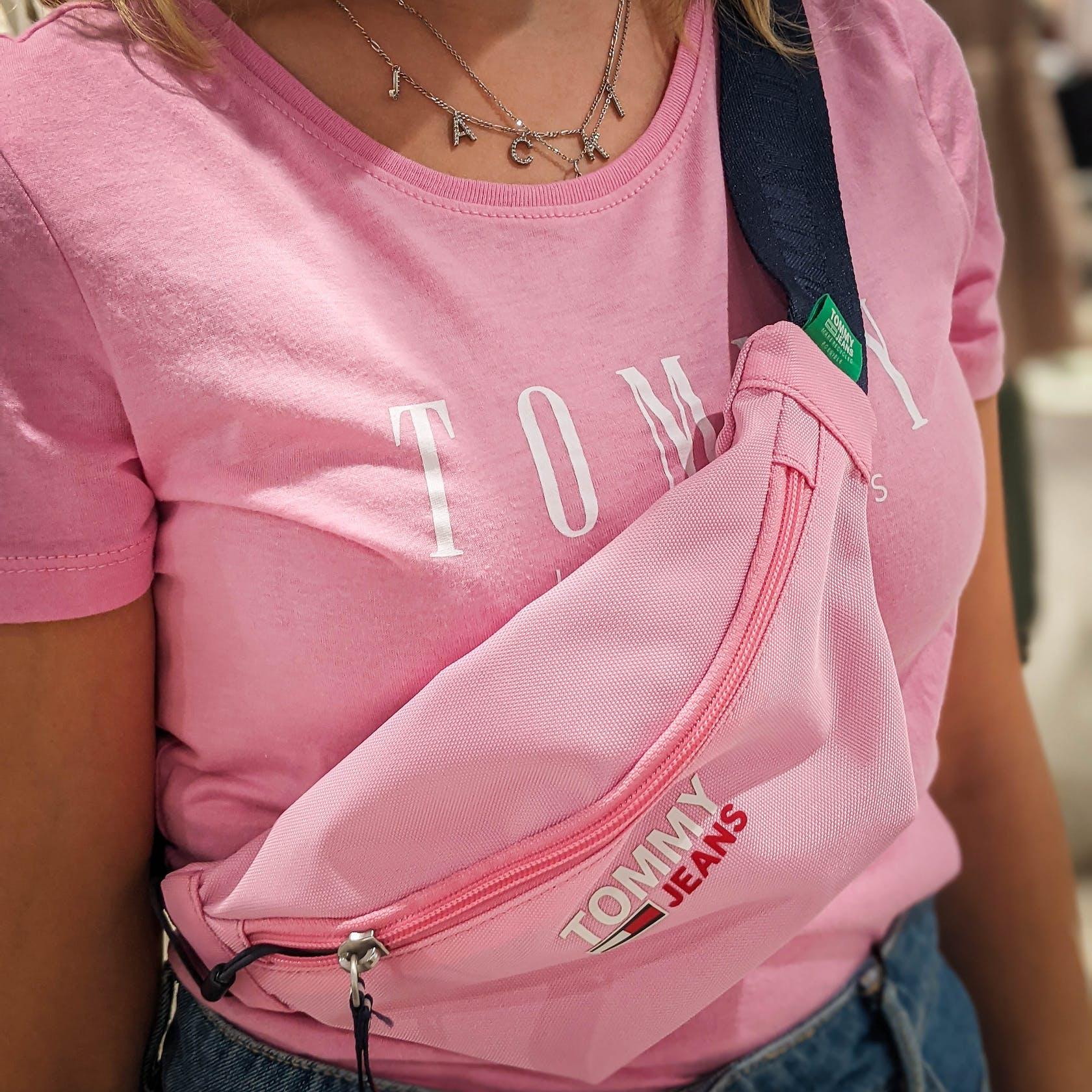 Nahaufnahme von einem pinken Tommy Jeans T-Shirt und einem Crossbody