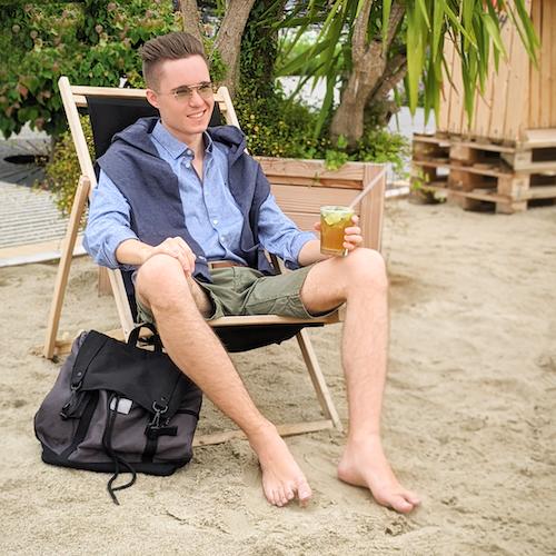 junger Mann in sommerlichem Outfit sitzt mit einem Getränk in der Hand am Strand