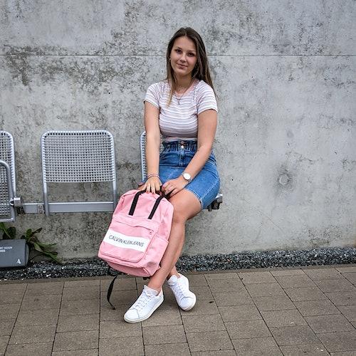 junge Frau sitzt draußen in einem sommerlichem Outfit.