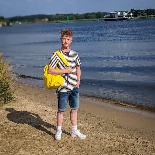 junger Mann steht in gestreiftem Shirt und Jeansshorts am Strand