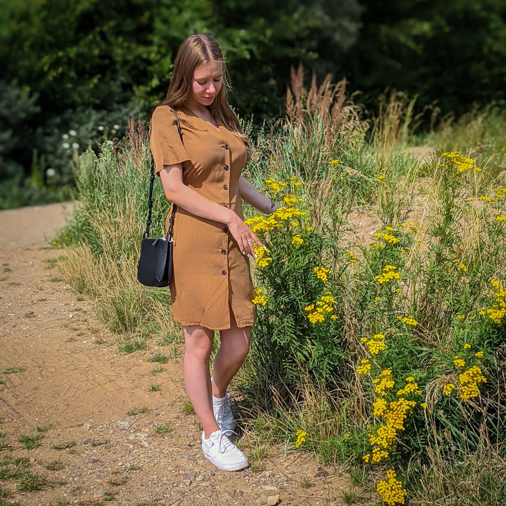 Junge Frau in Sommerkleid geht auf einem Sandweg spazieren