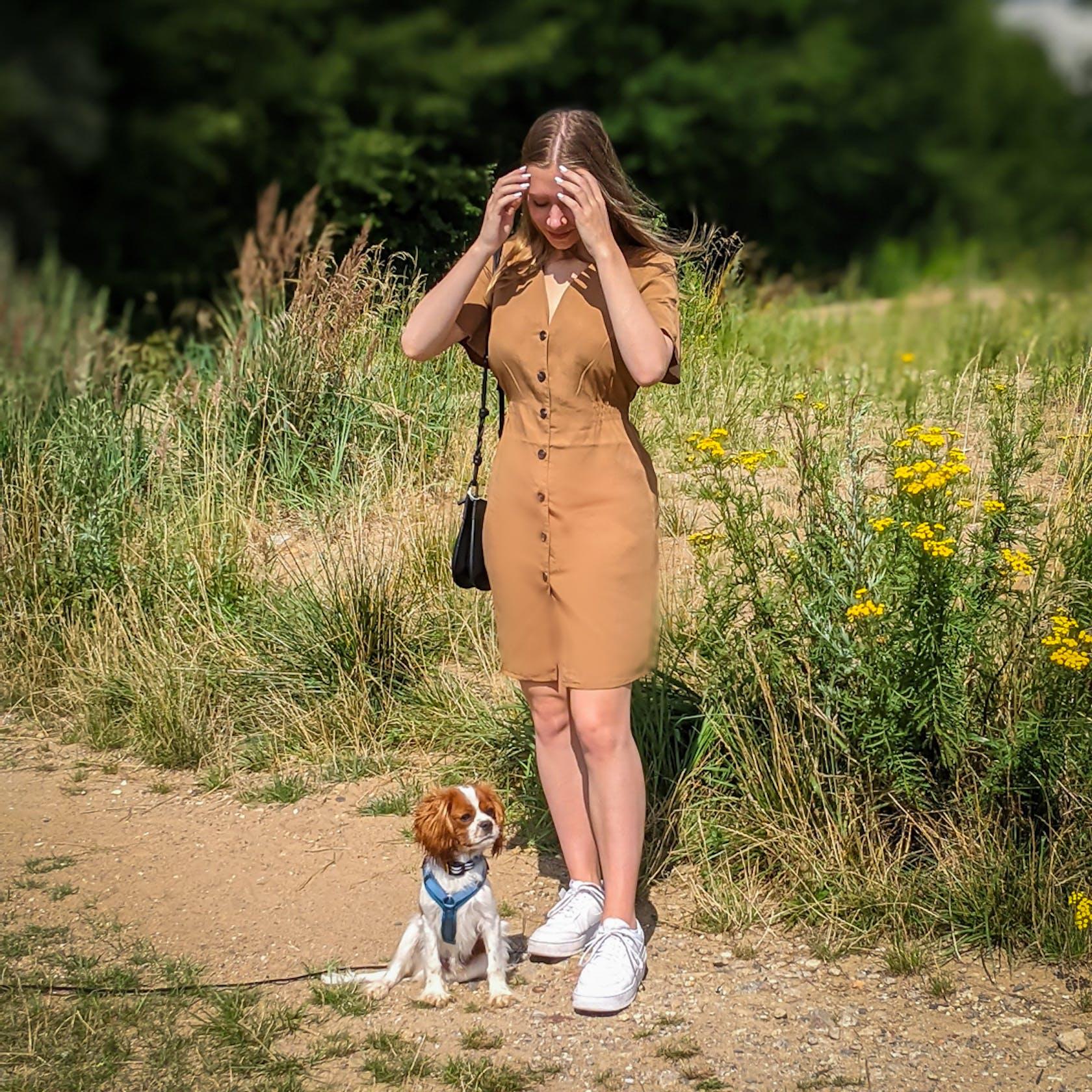 junge Frau steht mit kleinem Hund an einem Sandweg
