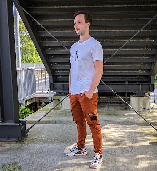 junger Mann trägt ein weißes T-Shirt, eine braune Cargohose, bunte Sneaker und steht draußen vor einer Treppe