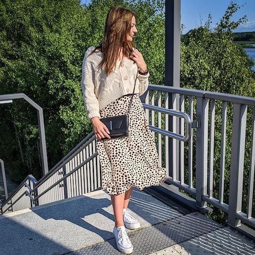 junge Frau steht in einem sommerlichem Outfit an einer Treppe und guckt in die Ferne