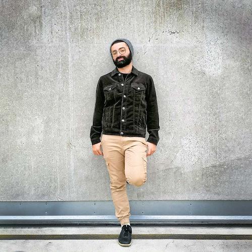 mann präsentiert sein outfit welches aus einer schwarzen Cordjacke und einer beigen Hose besteht