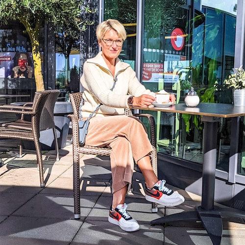 Frau sitzt in einem Cafe und trink einen Cappuchino. Dabei zeigt sie ihr Outift welches aus einem weißen Strickpullover und einer beigen Cordhose besteht.