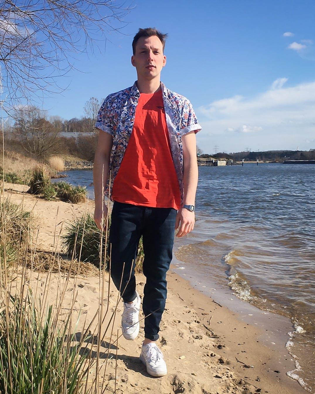 Mann geht in sommerlichem Outfit am Strand spazieren