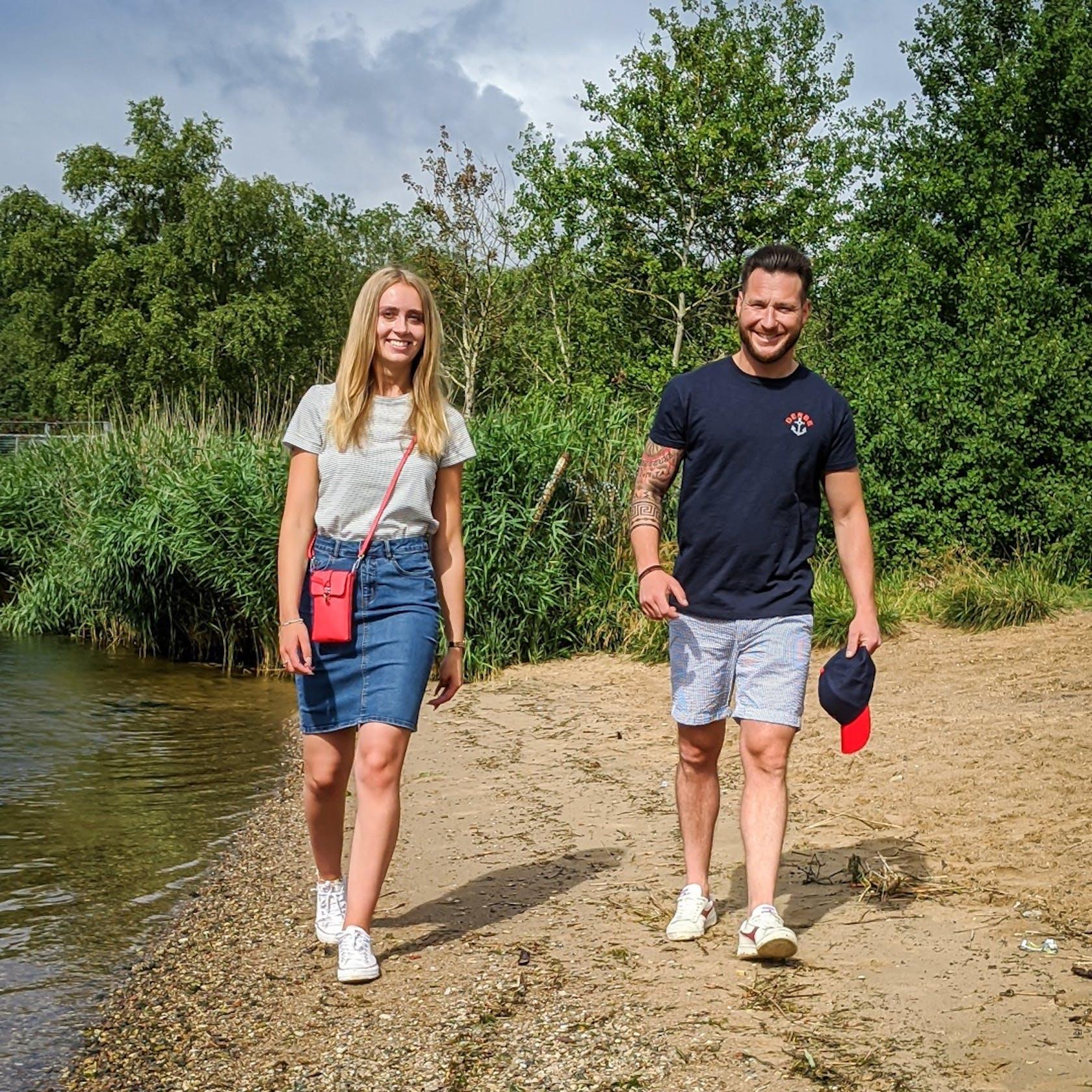 Mann und Frau zeigen Trend Outfits am Strand