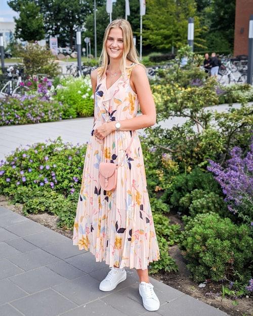 Eine junge Frau trägt ein langes Sommerkleid mit Blumenmotiv