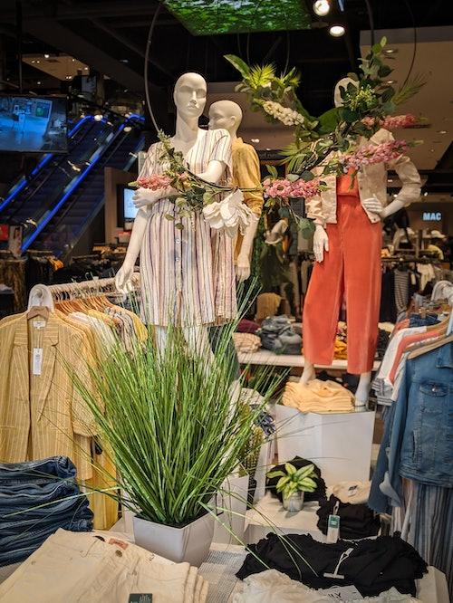 drei Schaufensterpuppen hinter zwei Kleiderständern und einem Tisch mit verschiedenen Kleidungsstücken