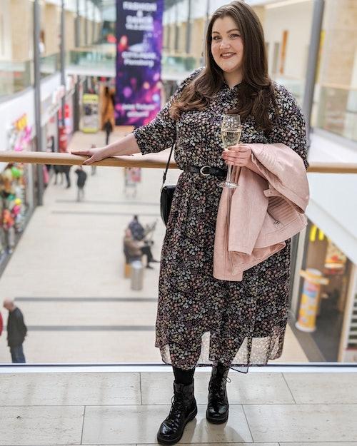 Frau in einer geblümten Bluse mit passendem Rock stehend in einer Shoppingmall