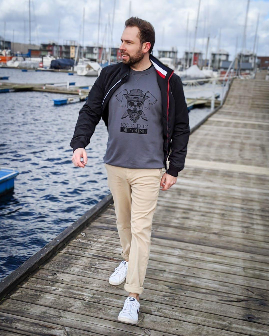 Mann läuft im modischen Outfit über einen Steg