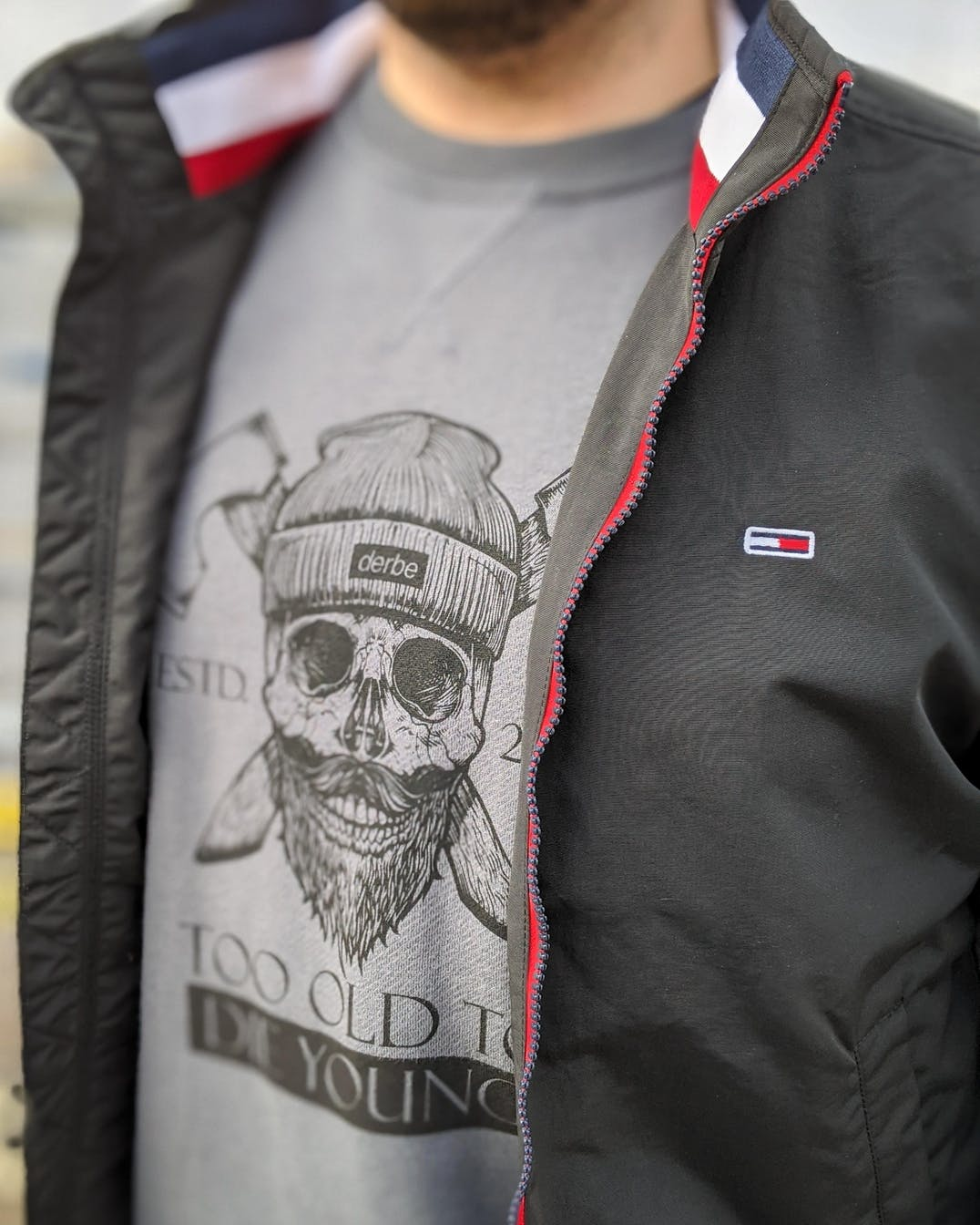 grauer Sweater von Derbe und schwarze Bomberjacke von Tommy Jeans in Nahaufname