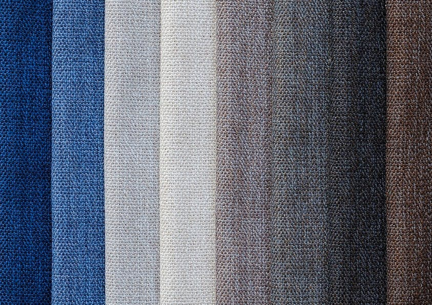 Acht Stoffbahnen in unterschiedlichen Farben nebeneinander gelegt.