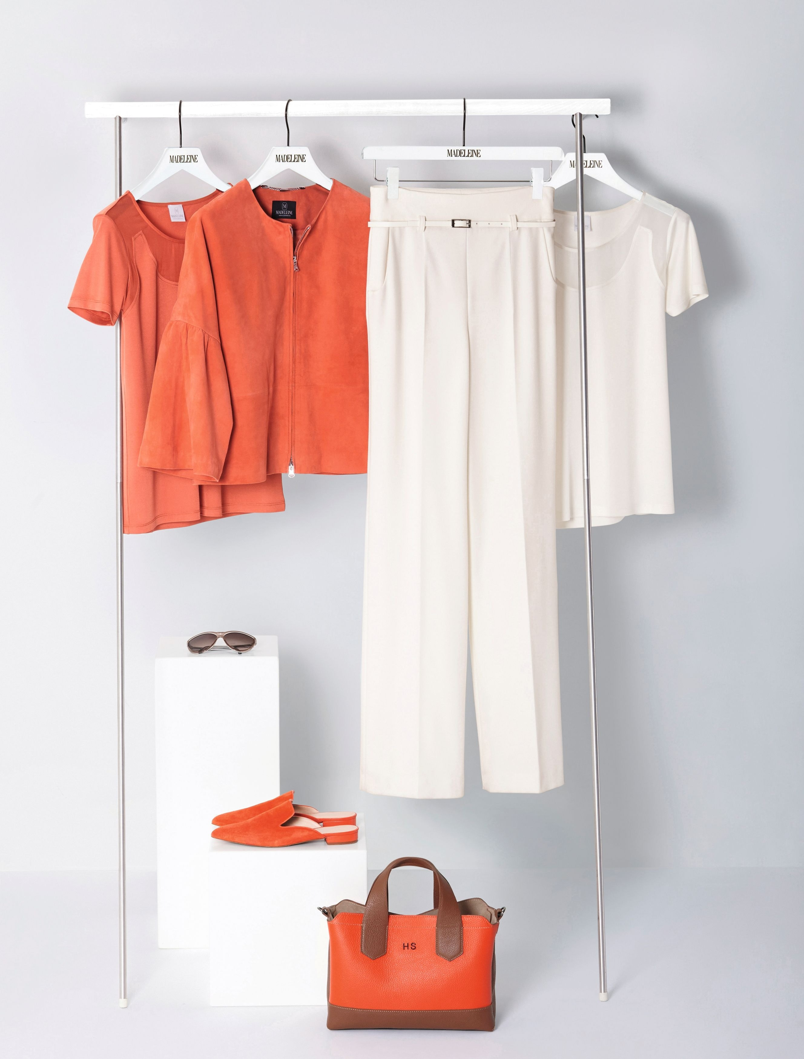 Verschiedene MADELEINE Artikel in Orange und Weiß auf einer Kleiderstange.