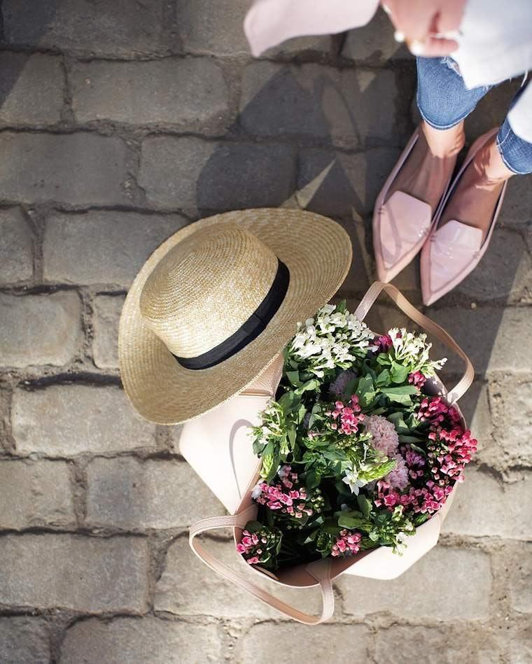 Ein Hut und eine Handtasche, die mit Frühlingsblumen gefüllt ist, von oben fotografiert auf Pflasterstein.