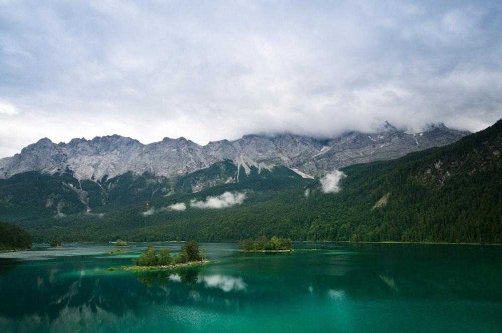 Der Eibsee in seiner ganzen Pracht: Wasser, Inseln, Wälder und im Hintergrund das Zugspitzmassiv.