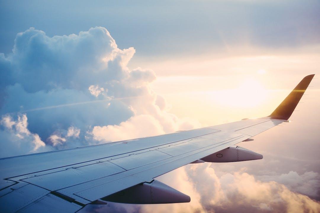 Flügel eines Flugzeuges zwischen Sonne und Wolken.