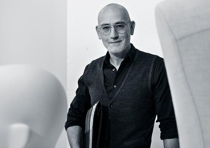 Ein Mann mit Glatze und Brille trägt Hemd und Weste sowie Aktenmappe unterm Arm.