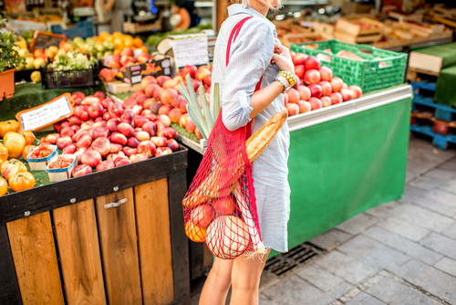 Woman walks through a fresh food market with a red net bag. Her bag holds fresh fruit, vegetables and a baguette.