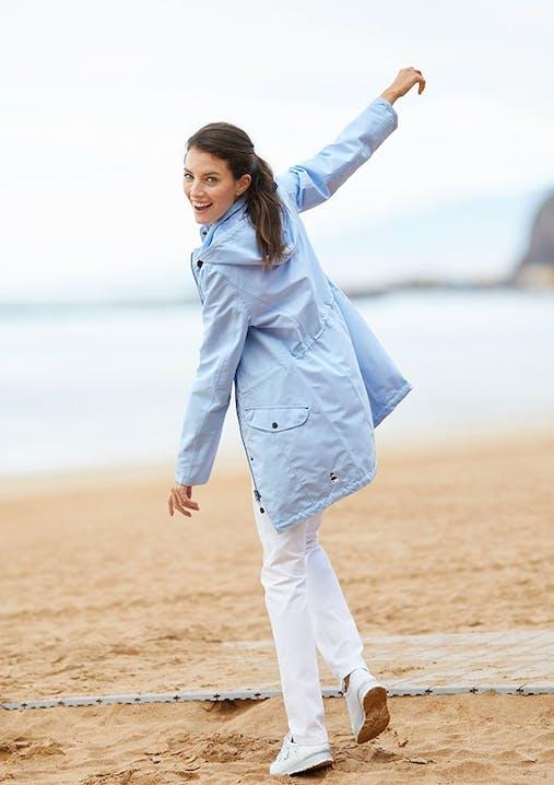 Lachende Frau mit weißer Hose und blauer Regenjacke tanzt am Strand.