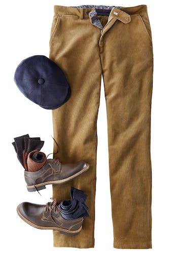 Braune Chino aus Cord mit blau-gemustertem Innenbund, braunen Schuhen mit gerollten Socken im Inneren und blaue Mütze.