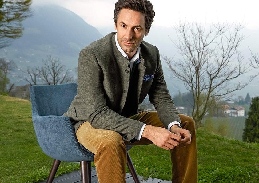 Mann mit dunkelgrüner Jacke und brauner Cordhose sitzt auf einem blauen Stuhl vor einer Wiese.