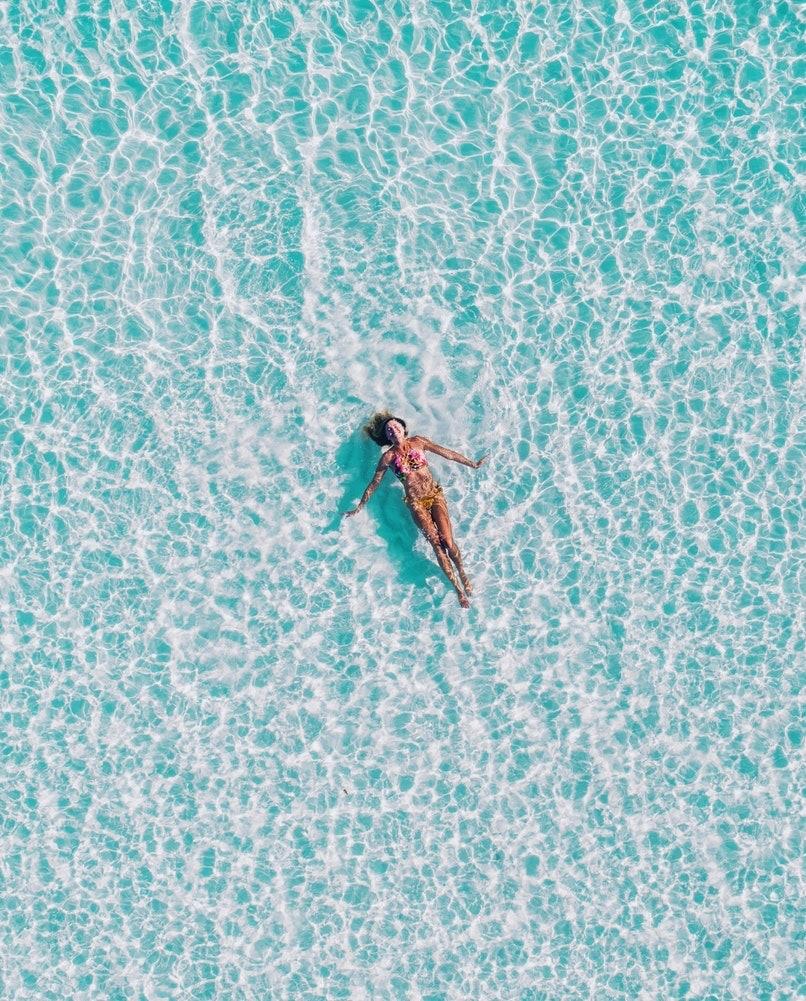 Frau lässt sich vom Meer treiben