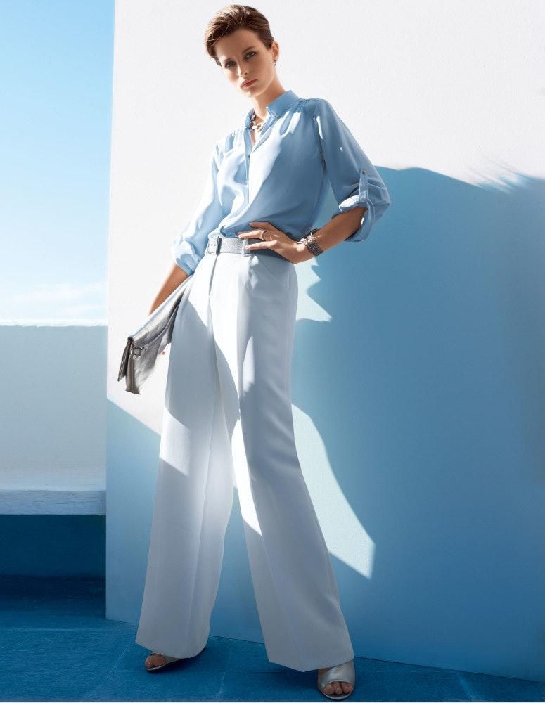 Frau mit weiter Bundfaltenhose an Wand stehend