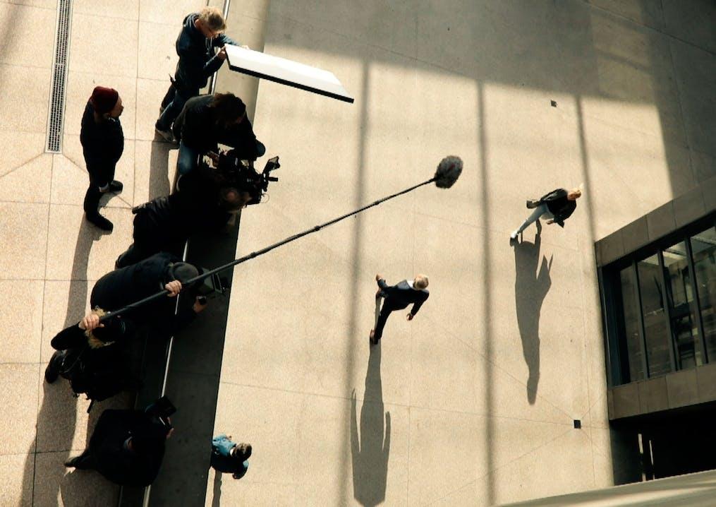 Frau und Mann gehen über einen Platz und werden von einem Kamerateam gefilmt.