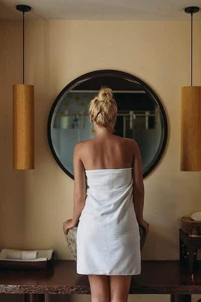 Valkoiseen pyyhkeeseen kietoutunut nainen, jonka vaaleat hiukset ovat nutturalla, katselee peilikuvaansa kylpyhuoneen peilistä.