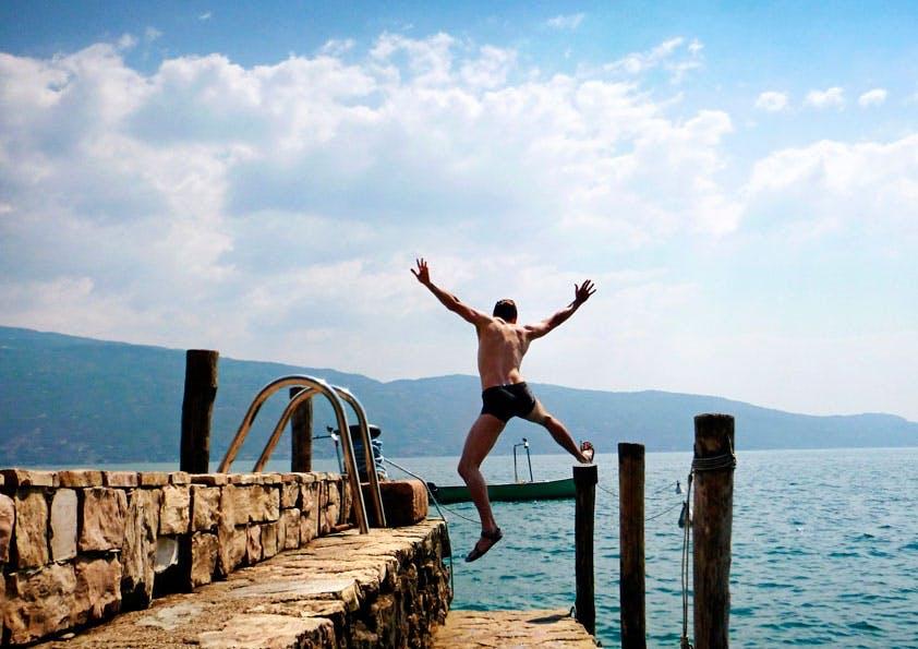 Mann in Badehose springt von einer Steintreppe ins Wasser.