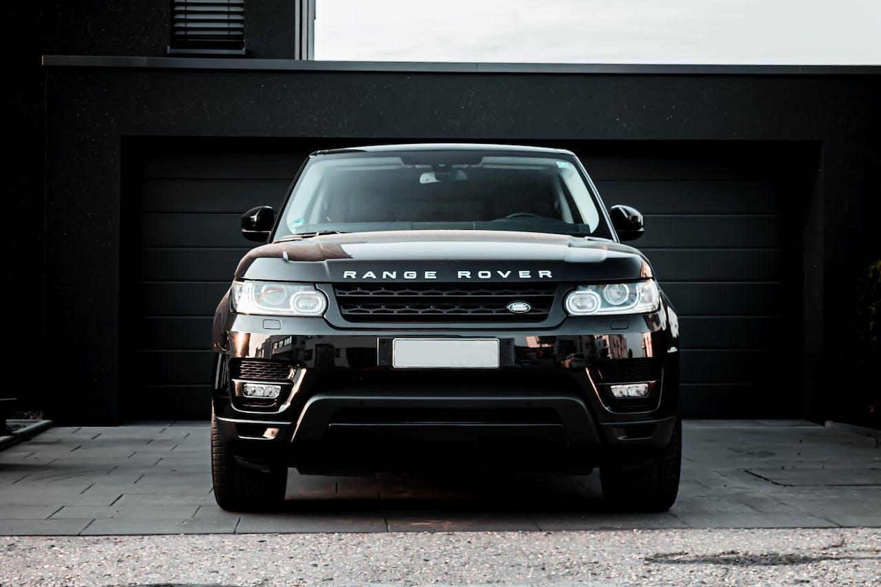 Range Rover SUV in schwarz in Einfahrt vor Garage. Möglich durch Land Rover-Leasing bei VEHICULUM