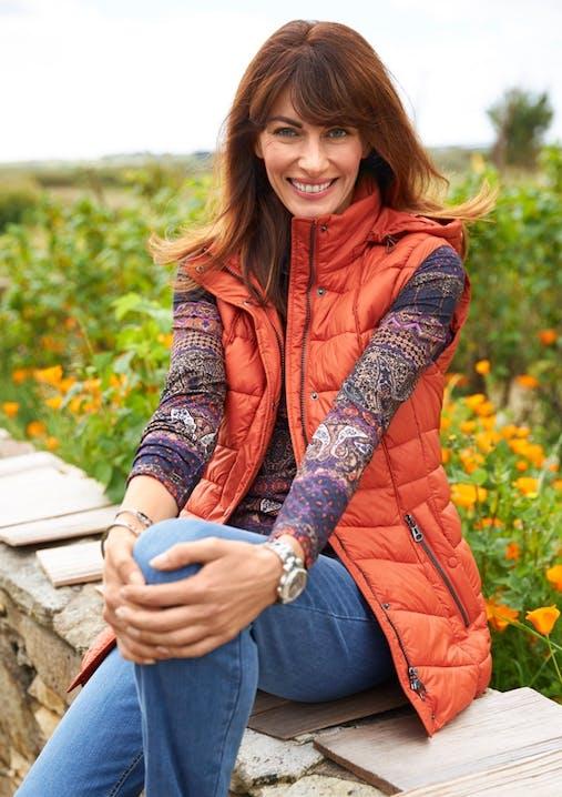 Frau mit braunen Haaren sitzt auf einer Mauer und trägt eine Jeans, ein gemustertes Oberteil und eine orangene Weste.