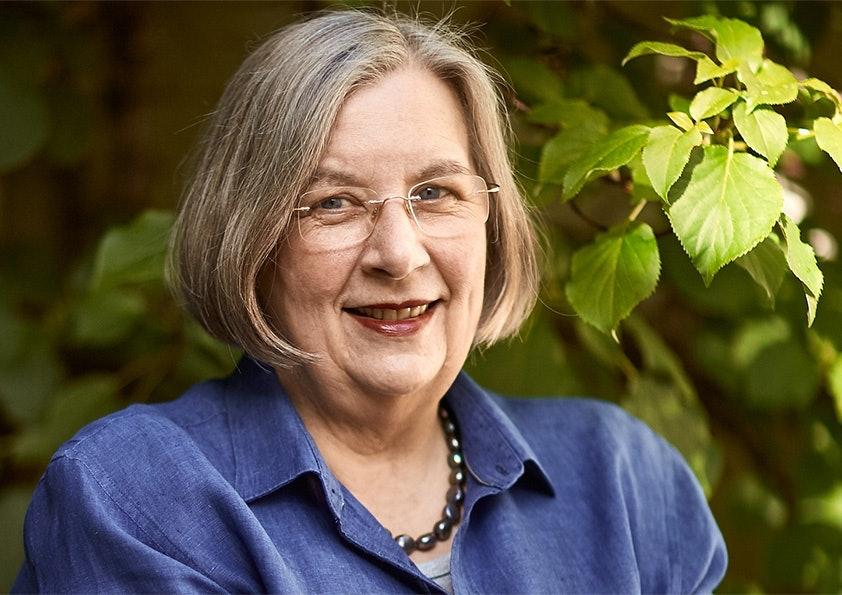 Frau mit kinnlangen Haaren, Brille und blauer Bluse lächelt.