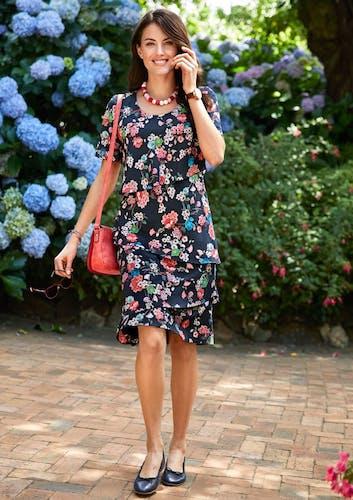 Eine Frau mit braunen Haaren steht vor einem Busch mit Blumen und trägt ein Kleid mit Blütenmuster.