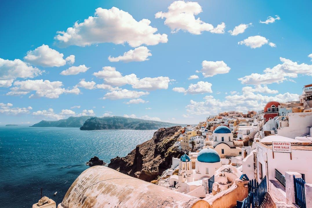 Blauer Himmel mit Wolken, darunter Meer und eine Stadt aus weißen Häusern mit blauen Kuppeln.