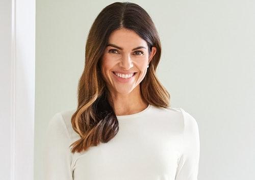 Frau mit braunen Haaren und weißem Oberteil lächelt freundlich.