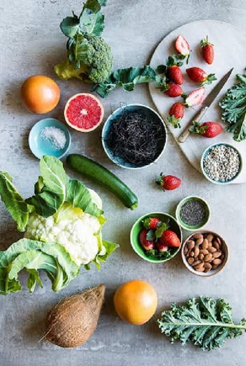 Kuva tuoreista vihanneksista, hedelmistä, pähkinöistä ja siemenistä sementtialustalla.