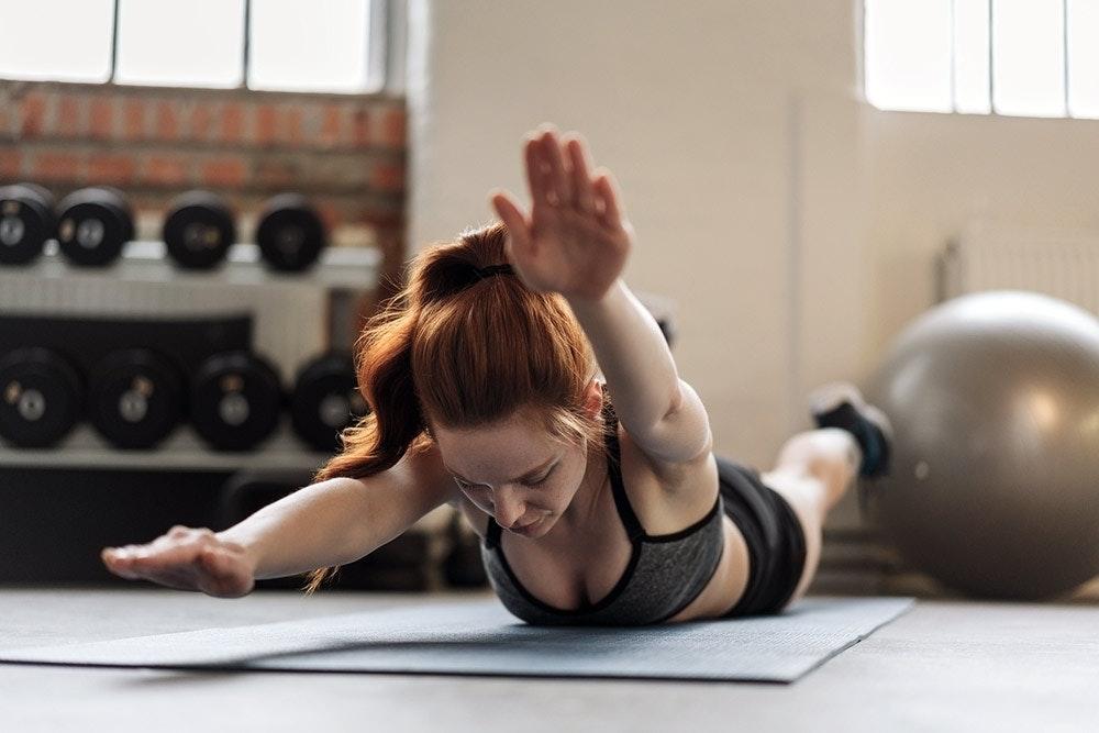 Junge Frau mit roten Haaren macht Rücken Workout