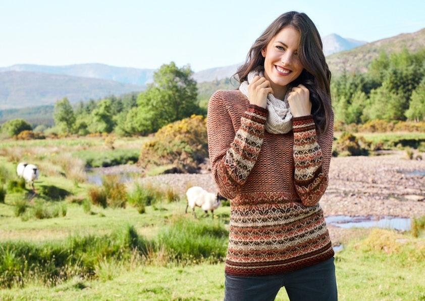 Im Vordergrund steht eine Frau mit braunen Haaren und lächelt. Sie trägt einen Pullover mit Strickmuster. Im Hintergrund ist eine grüne Landschaft mit Wald, Wiese, Schafen und blauem Himmel zu sehen.