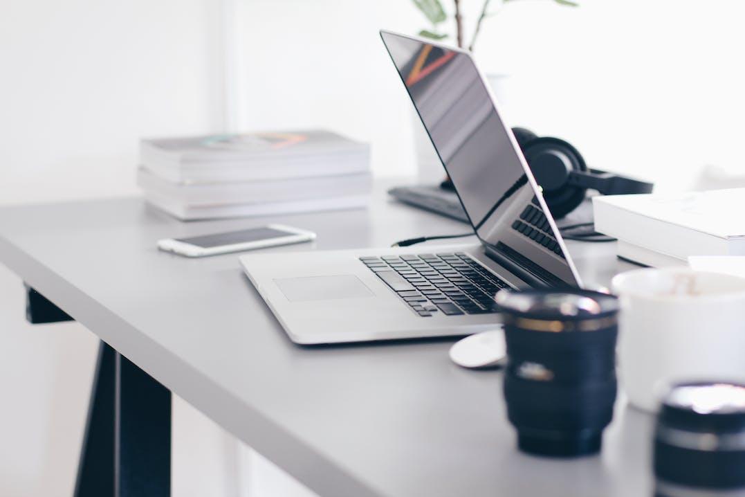 Halbgeöffneter Laptop, ein Handy, Bücher, Kopfhörer und eine Tasse auf einem grauen Tisch.