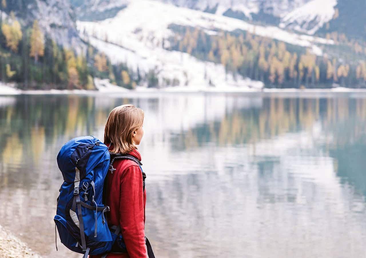 Frau mit Wanderrucksack am See