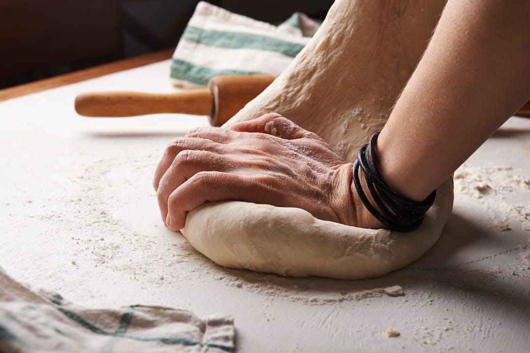 Mann knetet Brotteig
