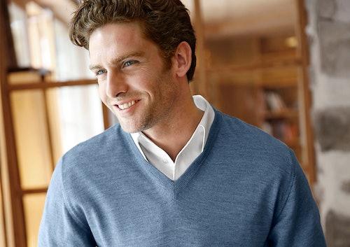 Mann mit weißem Hemd und blauem V-Pullocer lächelt.