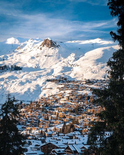 Festlich beleuchtetes Dorf am Fuße schneebedeckter Hügel