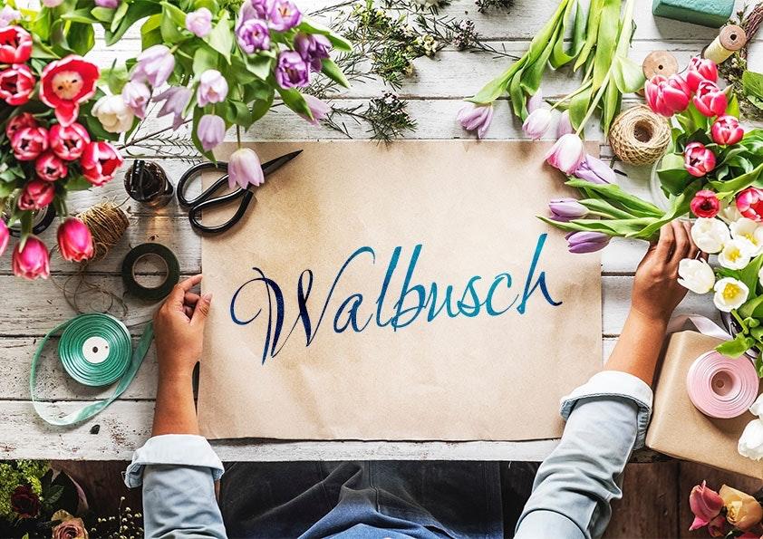 Braunes Papier mit blauer Aufschrift auf einem Holztisch, umgeben von Blumen. Eine Hand greift zu einer Tulpe, die andere liegt auf dem Tisch.
