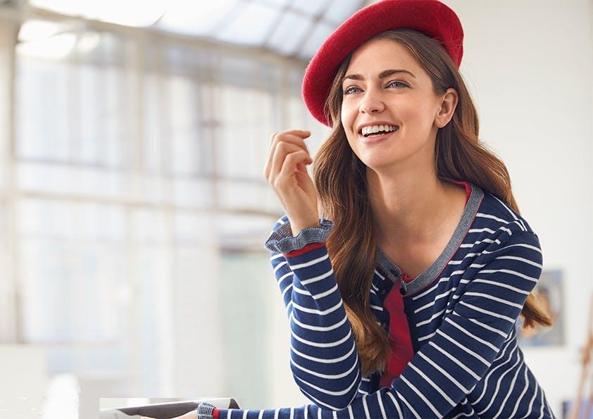 Sitzende Frau mit langen braunen Haaren, roter Baskenmütze und blau-weiß gestreifter Strickjacke lacht in die Kamera.